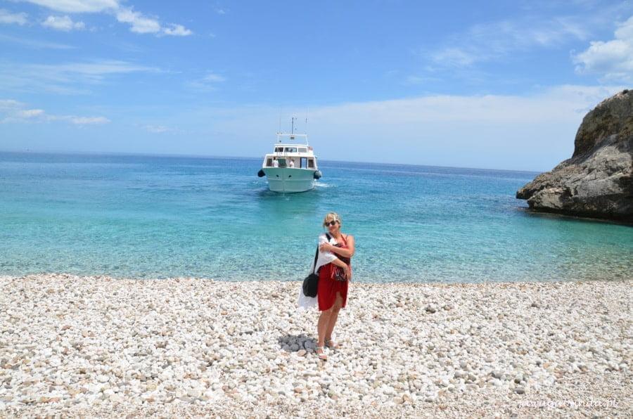 kobieta stoi na kamienistej plaży w tle statek