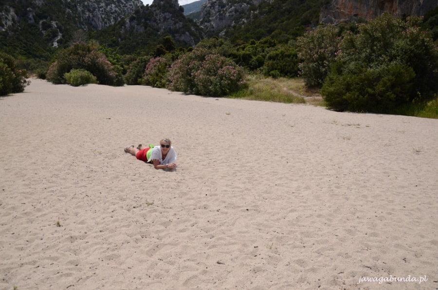 kobieta leży na kamienistej plaży