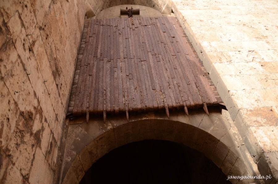 żelazne drzwi z kolcami nad bramą