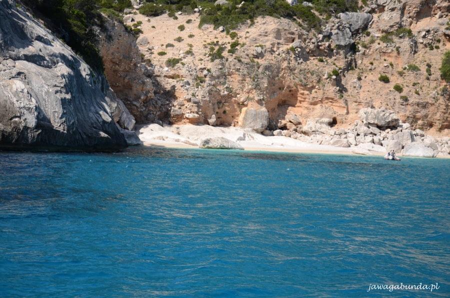 mała plaża z białymi kamieniami a nad nią skały, przed nią błękit morza