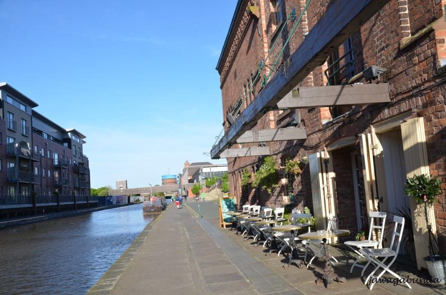 chodnik wzdłuż kanału. z boku zabudowania domów i restauracja