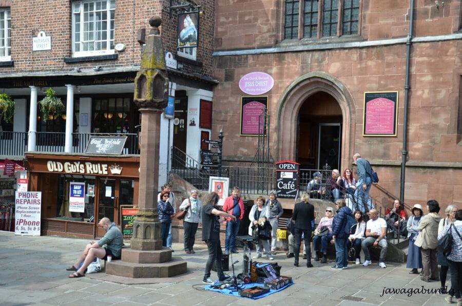 ludzie wokół obelisku i człowiek grający na skrzypach