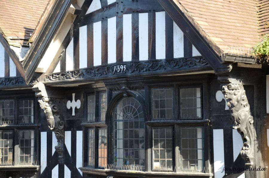 okno z małymi szybkami i drewniana elewacja domu