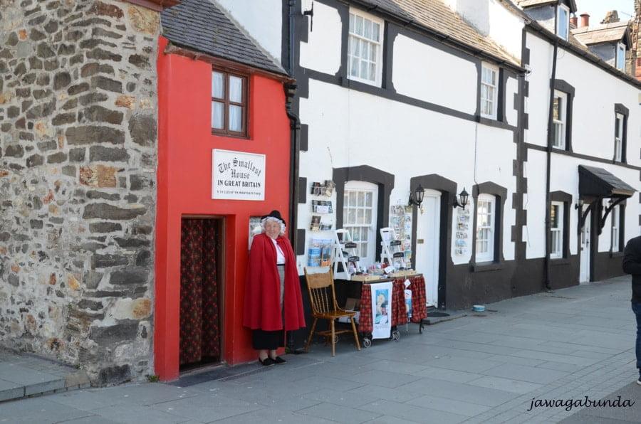 mały czerwony dom i kobieta ubrana na czerwona