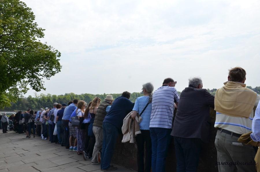 ludzie widoczni od tyłu a stojący przy murach miejskich