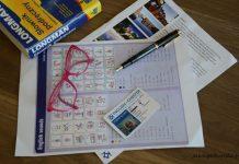 słownik, pióro i okulary na kartce z językiem angielskim