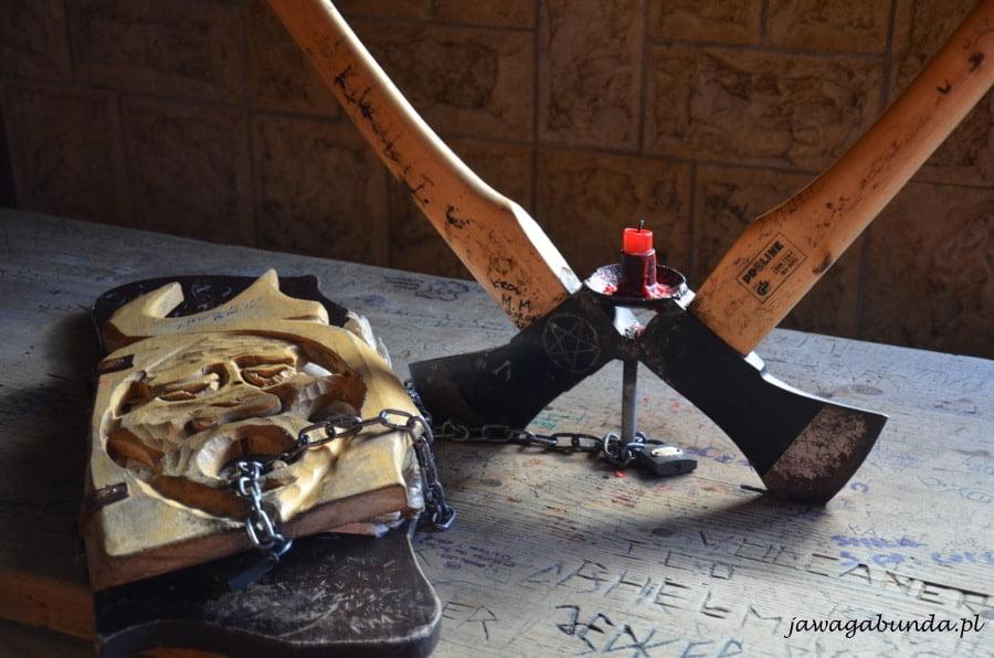 dwie siekiery wbite w stół i księga z drewnianą okładką diabła