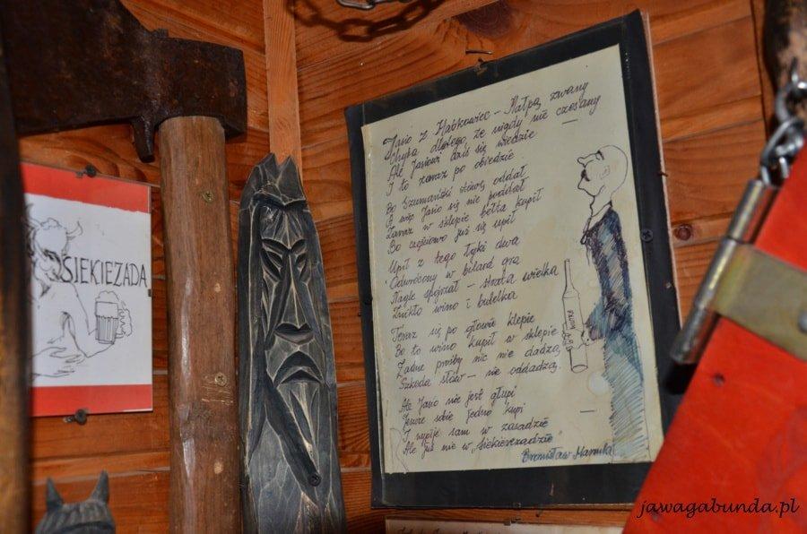 rzeźba i wiersz oprawiony w ramkę wiszą na ścianie