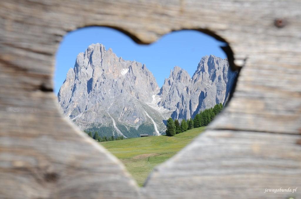 widok na góry przez serce wycięte w drewnie