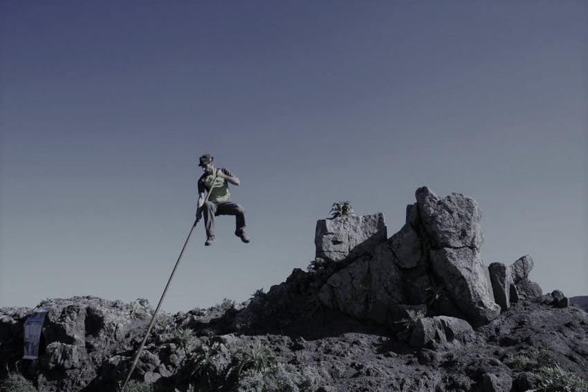 mężczyzna skaczący o tyczce w górach