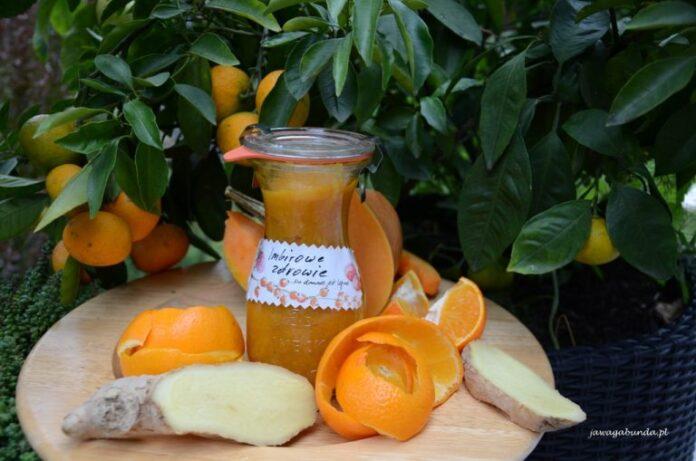 Piękny pomarańczowy dżem dyniowo pomarańczowy z imbirem. Dżem w wysokim słoju na stole z pomarańczą i imbirem.