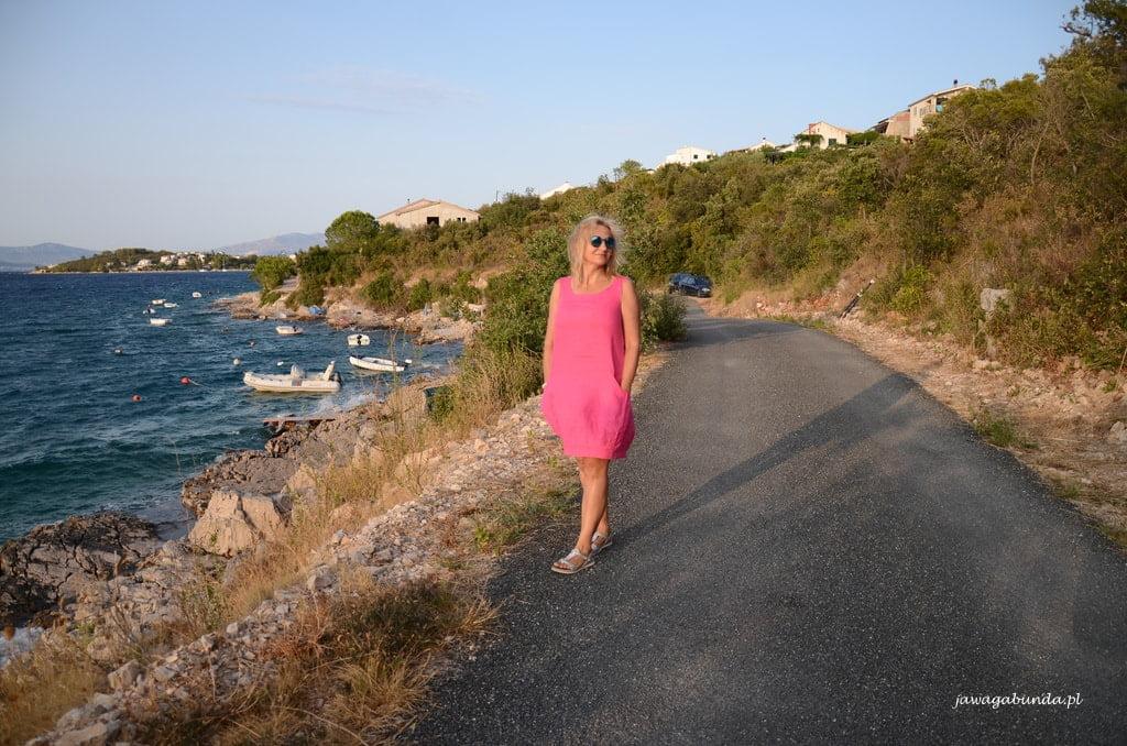 kobieta w malinowej sukience nad brzegiem morza