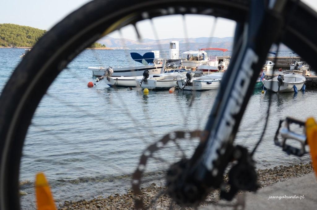 koło roweru na pierwszym planie, z tyłu morze i jachty