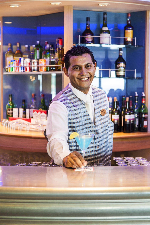 barman podaje kieliszek z napojem w barze