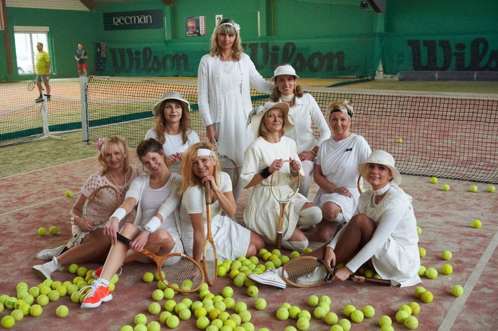 kobiety w strojach tenisowych siedzące wśród rozsypanych piłeczke