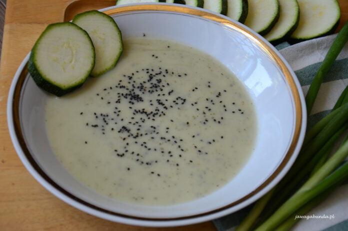Zupa krem z cukinii podana w talerzu razem z dwoma plastrami cukinii.