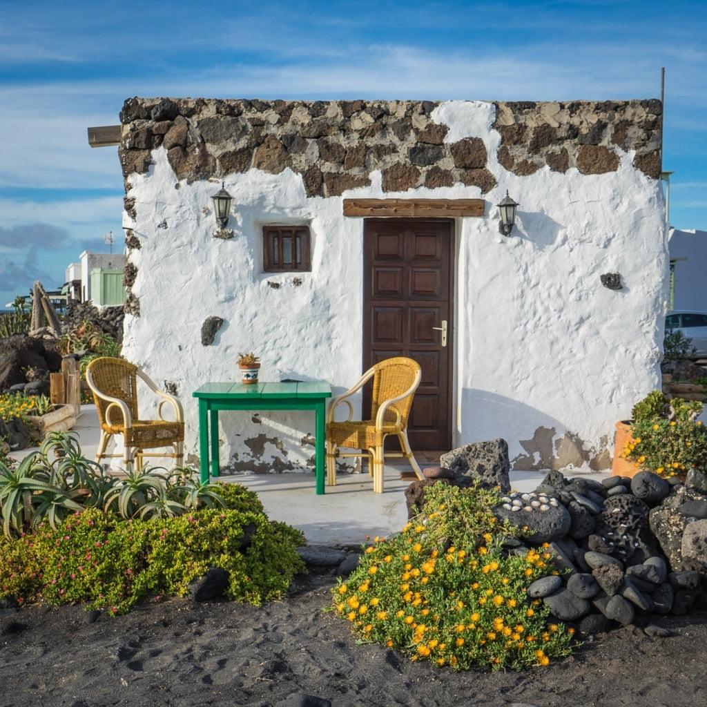 mały domek z kamienia i dwa krzesła
