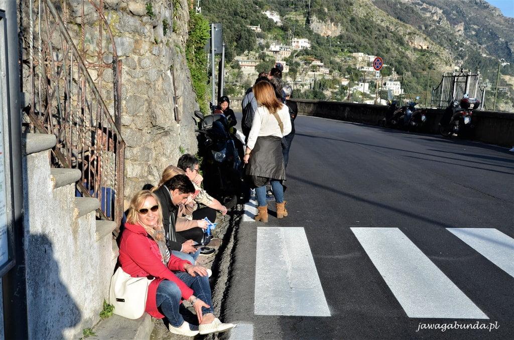 ludzie siedzą na krawężniku