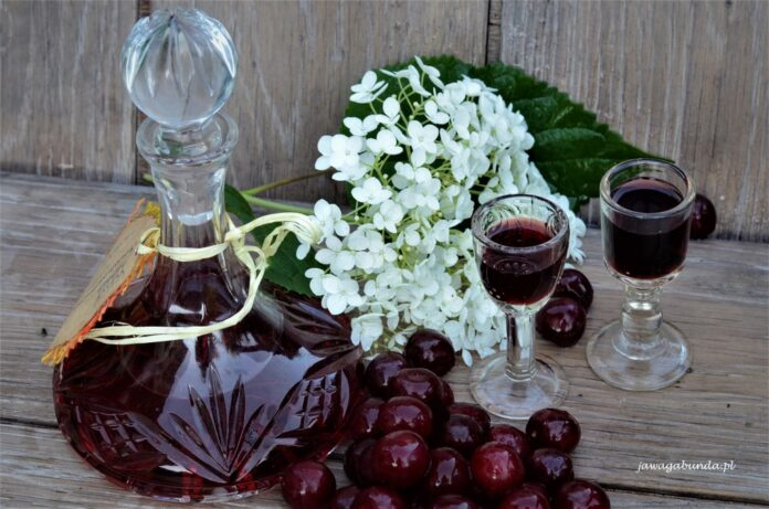 Nalewka wiśniowa w towarzystwie kwiatów pięknie podana w kryształowych kieliszkach. Wiśniówka o pięknym bordowym kolorze.