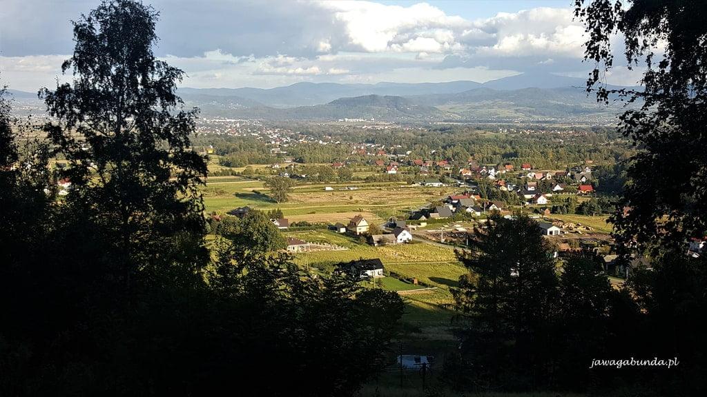 widok doliny z domami widoczny zza drzew