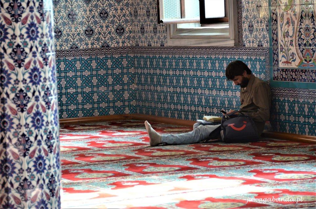 mężczyzna siedzi na podłodze w meczecie