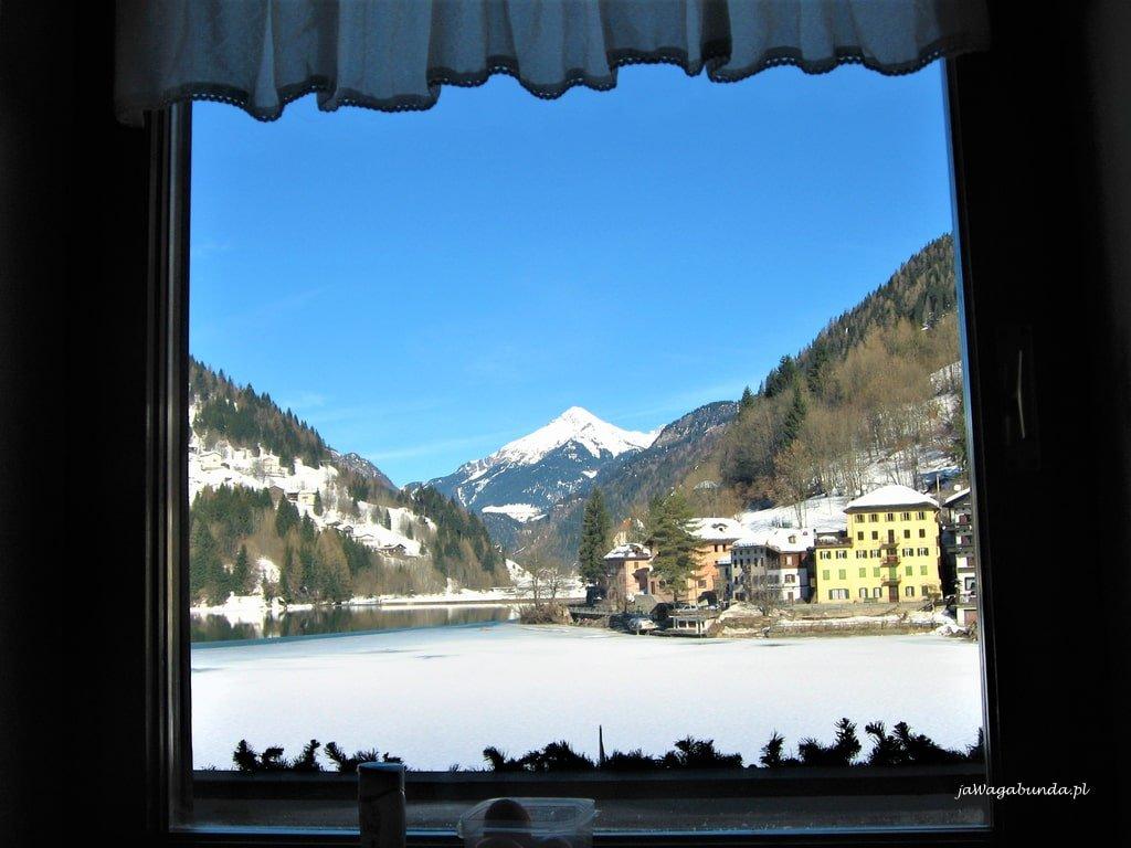 widok przez okno na stok i zamarznięte jezioro