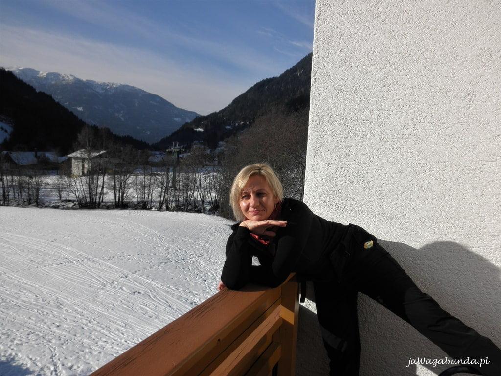 kobieta na balkonie a pod nim stok narciarski zaśnieżony