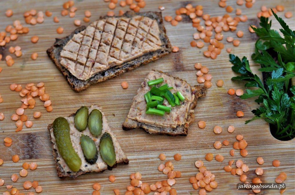 Pasta humus z czerwonej ciecierzycy na kromkach chleba na desce.