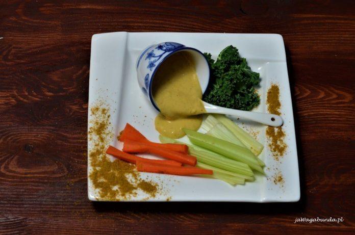Majonezowy sos curry podany na talerzu wraz z warzywami do maczania w sosie.