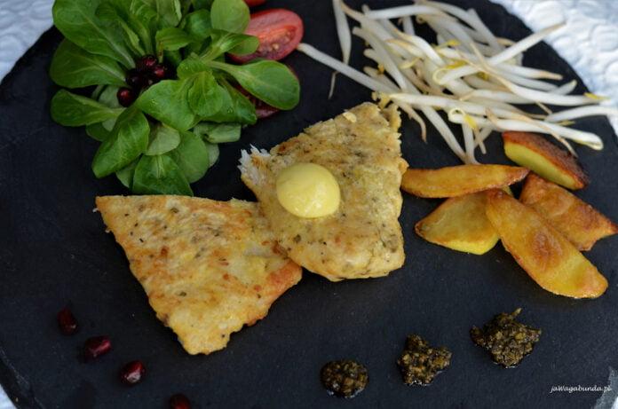 Filety z ryby usmażone w panierce z mąki i jajka podane wśród dodatków.