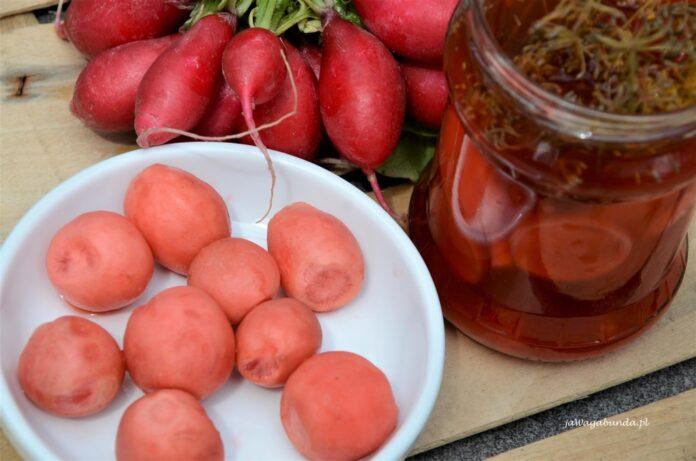 Kiszona rzodkiewka traci swój kolor ale woda w słoiku i sama rzodkiewka zachowuj smak. Rzodkiewki wyłożone na talerzu obok słoika z kiszonką.