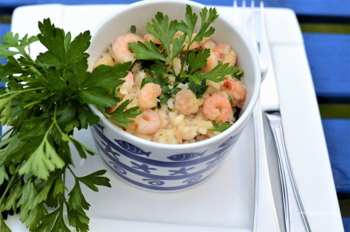 Krewetki z ryżem podane w niebieskiej miseczce.