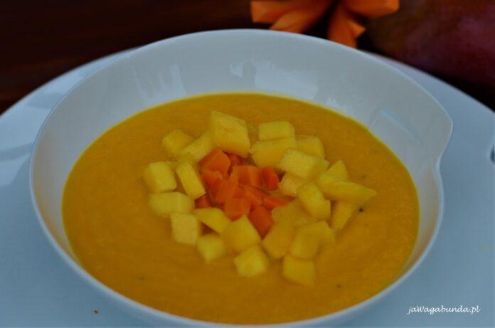 Zupa z marchwi podana z drobno pokrojonym owocem mango w białym talerzu.