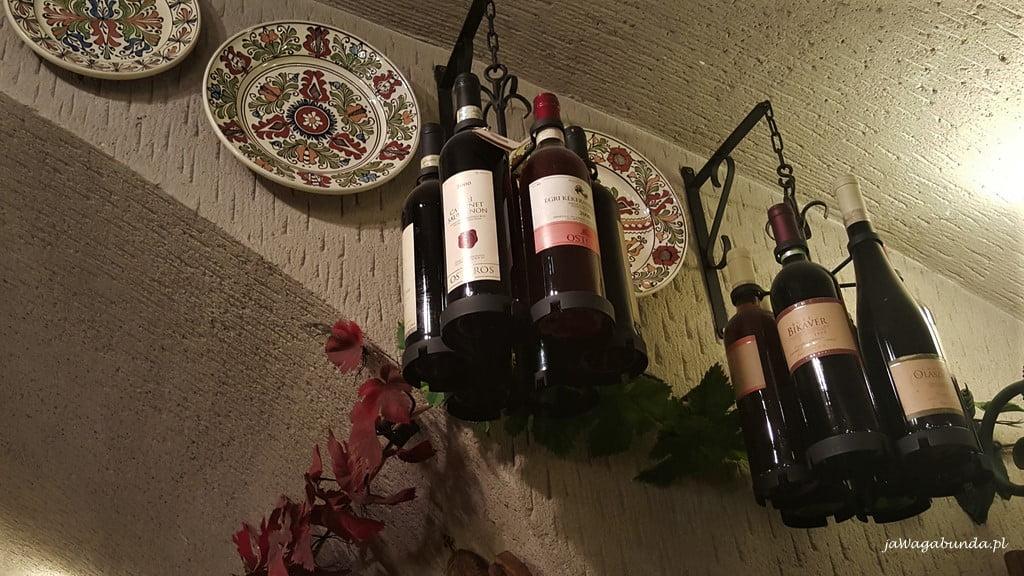 butelki z winem wiszące na stojakach pod sufitem