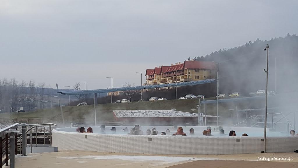 ludzie siedzą w gorących źródłach, a wokół śnieg