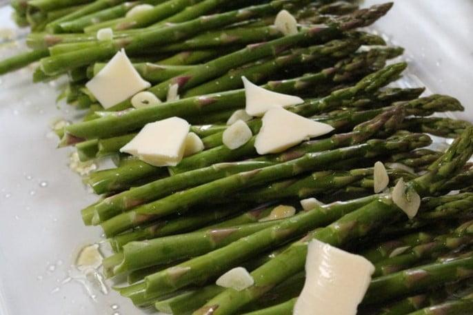 Szparagi posypane serem i gotowe do pieczenia w piekarniku.