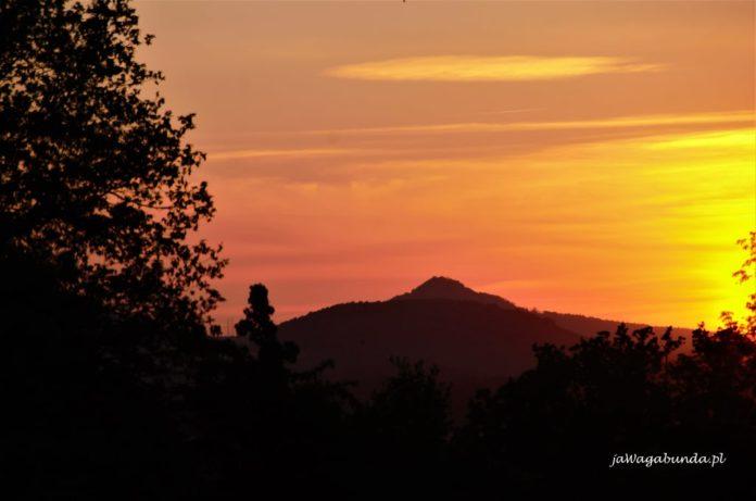 Wierzchołek góry Ostrzyca wulkan o zachodzie słońca na tle żółtego nieba