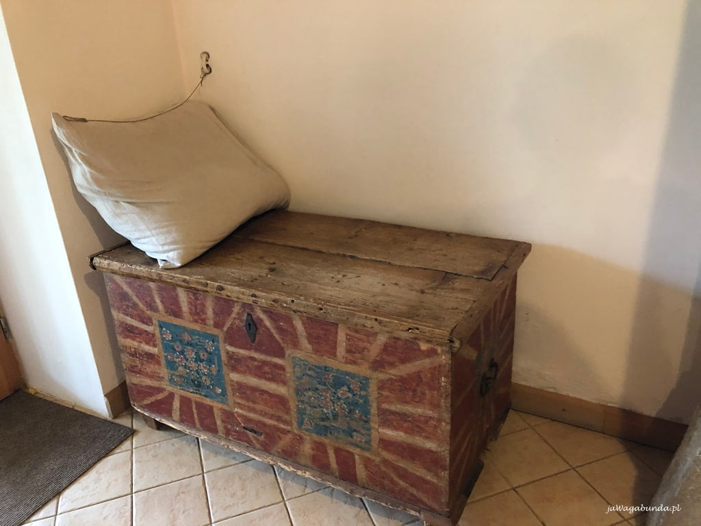 stara malowana skrzynia z poduszką, która jest wyposażeniem jadalni w domu w Pokrzywniku