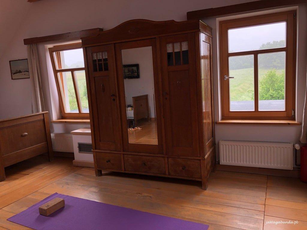 stara szafa i mato do ćwiczenia jogi na drewnianej podłodze