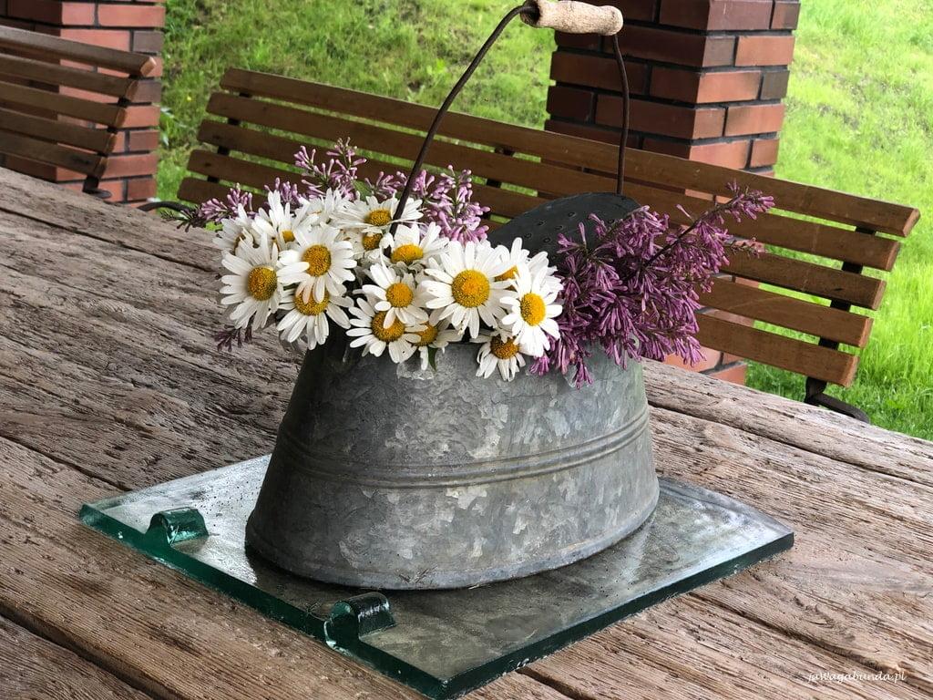 świeże kwiaty w cynowym naczyniu na stole