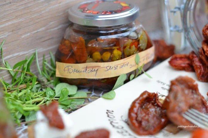 Suszone pomidory w oleju w słoiku oraz na talerzu.