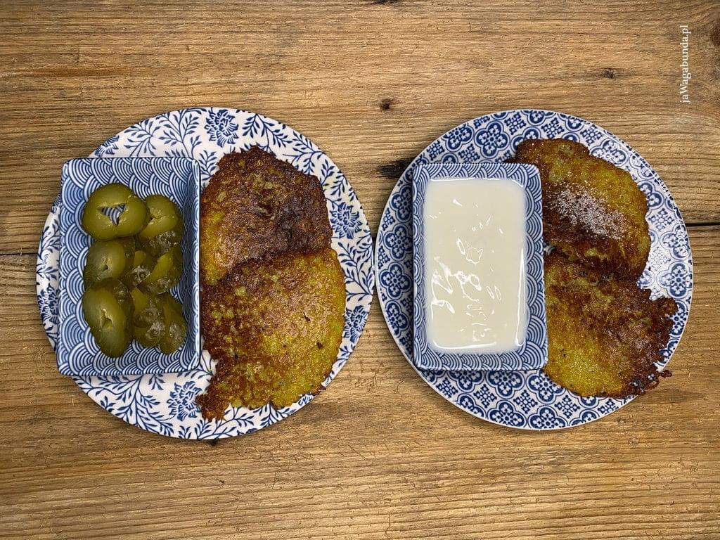 placki ziemniaczane podane na talerzu z ogórkiem kiszonym i śmietaną