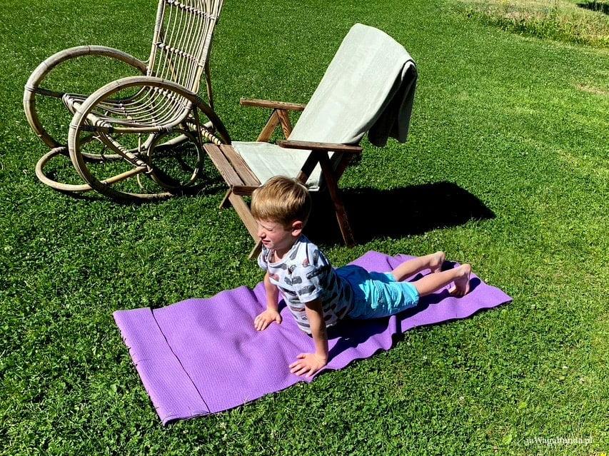 dziecko praktykujące jogę na macie na łące