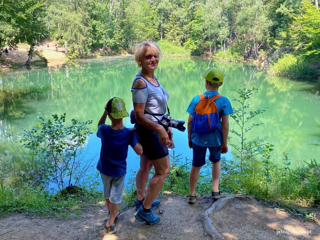 kobieta i dwójka małych dzieci nad kolorowym jeziorkiem o kolorze mocno błękitnym