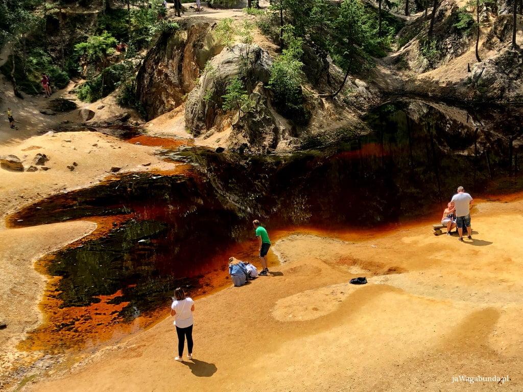 Jeziorko o rdzawej wodzie otoczone piaskowymi skałami