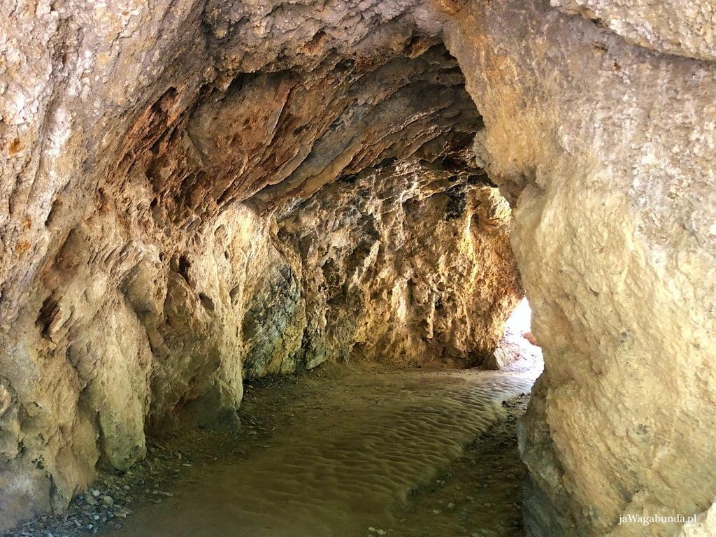 przejście pod skałami, tunel w żółtych skałach