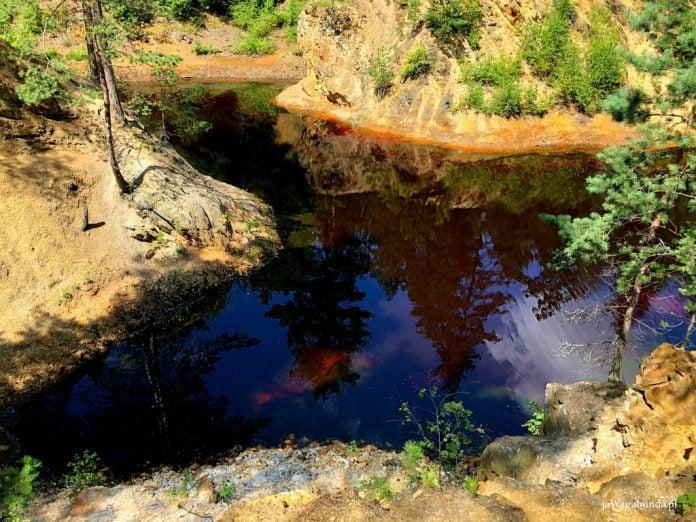 jezioro z kolorową wodą, w której odbijają się skały i drzewa
