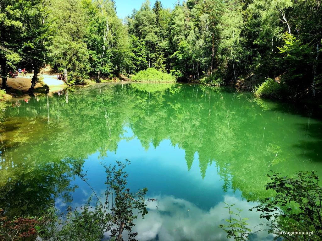 jeziorko o błękitnej wodzie otoczone lasem
