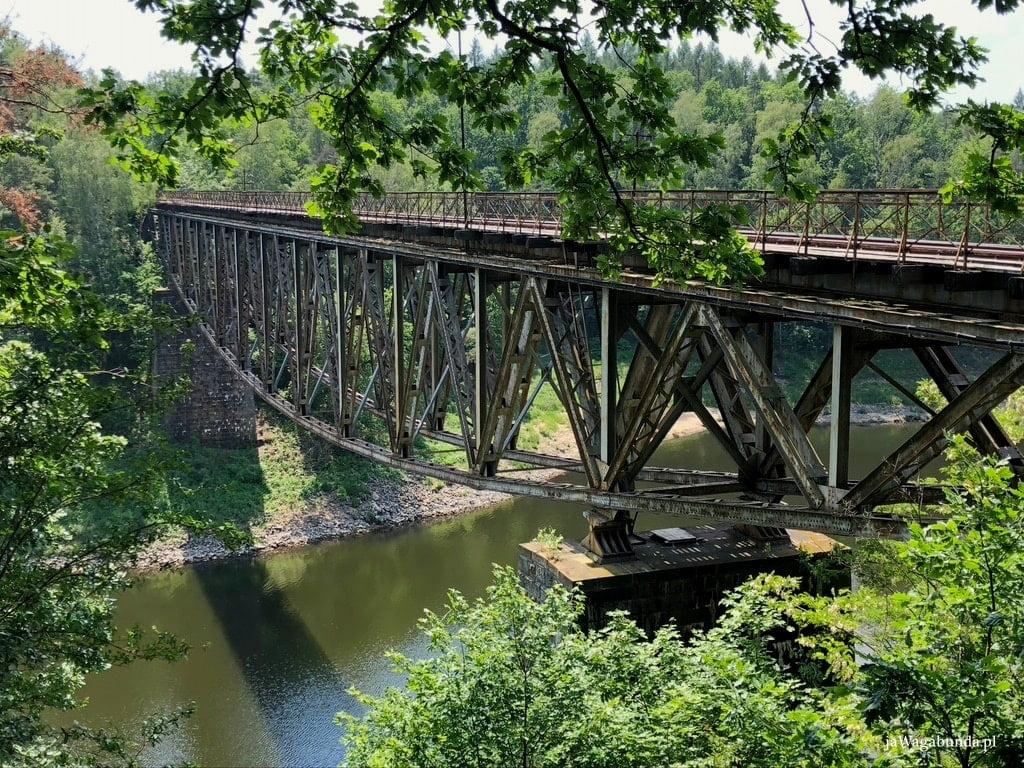 żelazny most z przęsłami skierowanymi w kierunku rzeki, położony nad rzeką