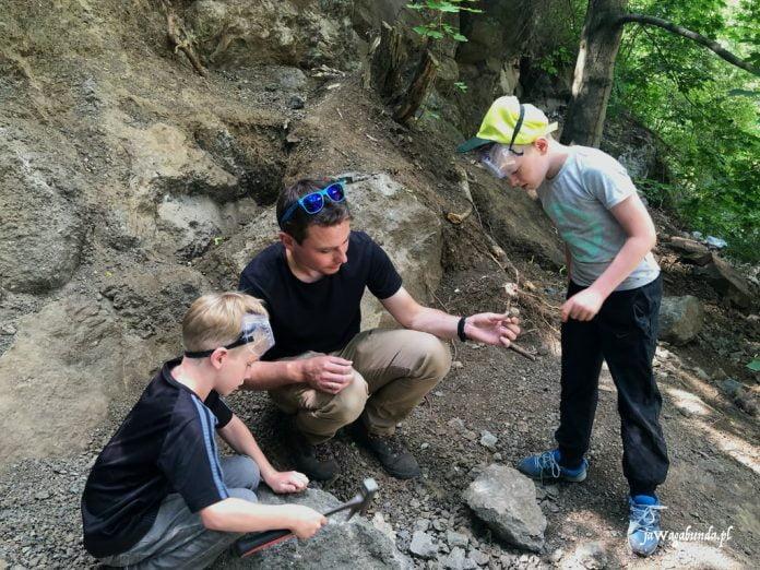 mężczyzna i chłopcy w skałach szukają agatów